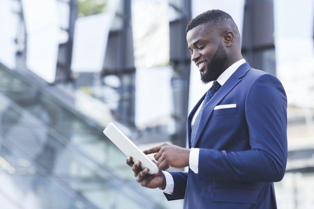 Pleased Black Businessman Using Digital Tablet Standing Outdoors, Copy Space